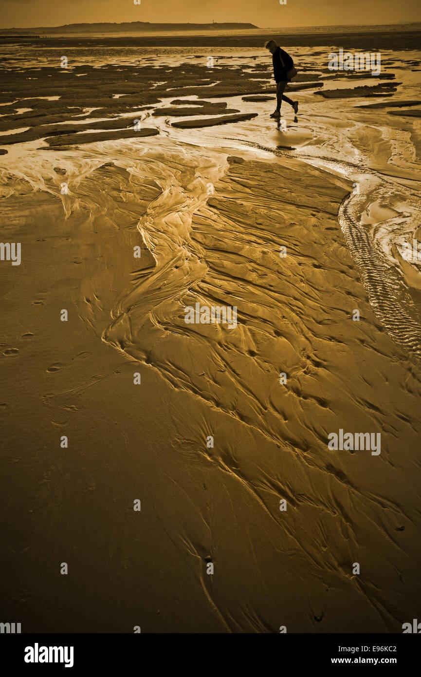 La figure unique de marcher sur une plage de sable mouillé Photo Stock