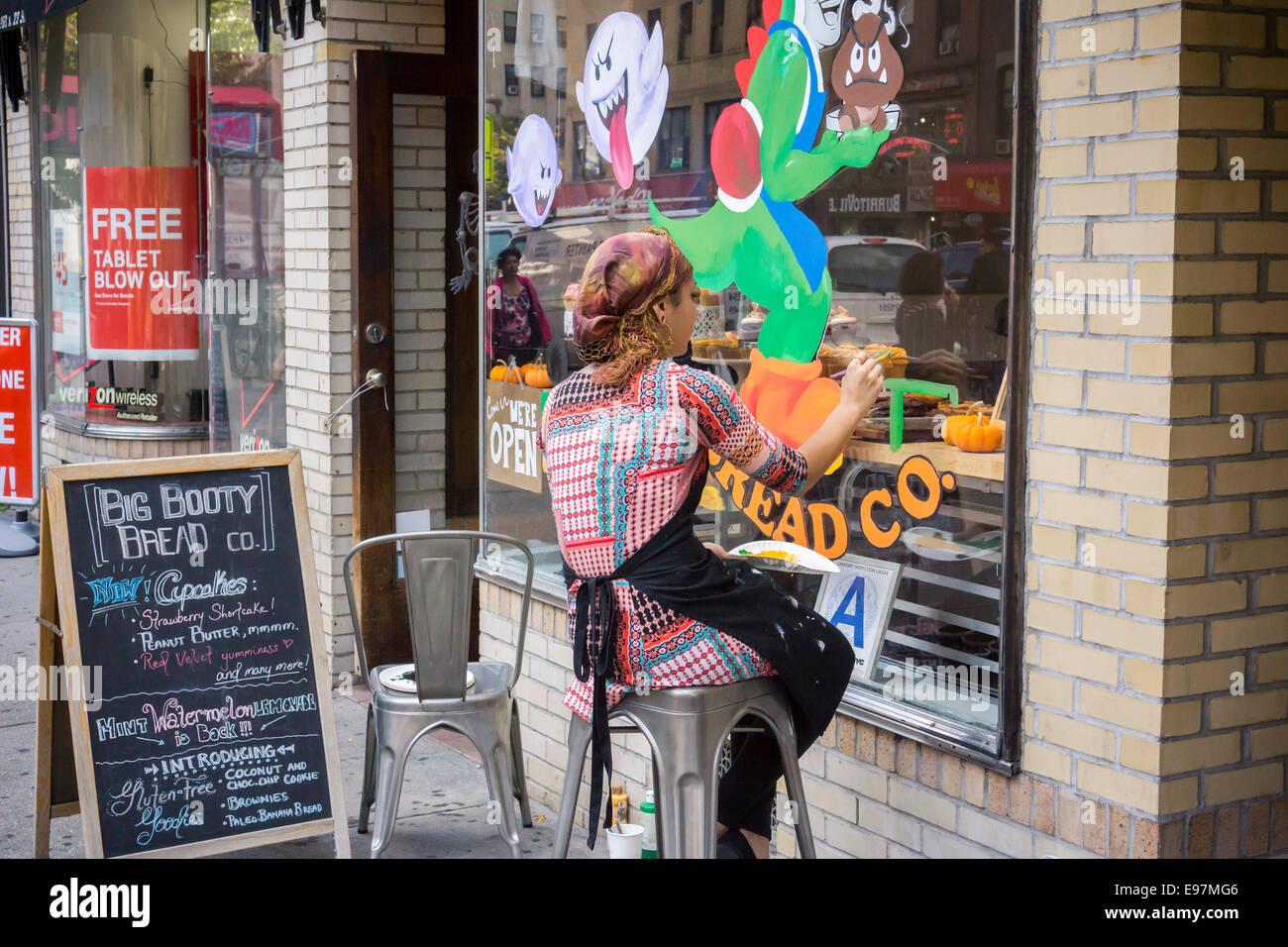Un peintre d'enseignes ornent la fenêtre du Big Booty bakery Bread Co. à Chelsea à New York Photo Stock