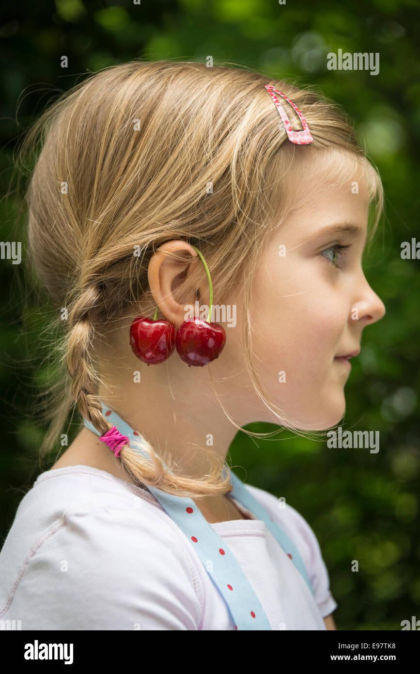 Petite fille, les cerises se balançant d'oreilles Photo Stock