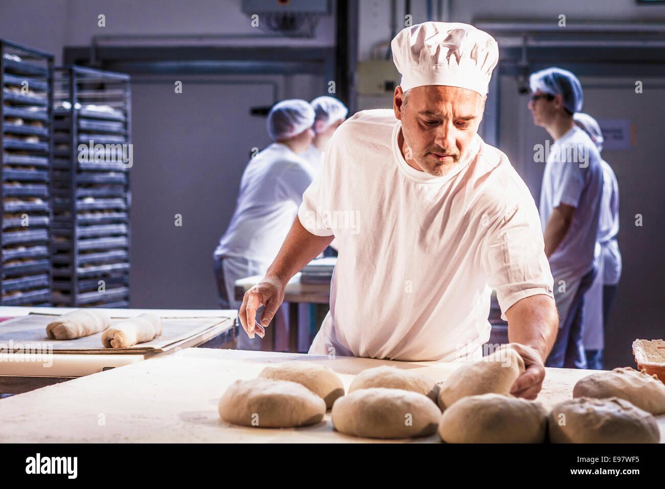 La cuisson du pain, chef contrôlant la pâte Photo Stock