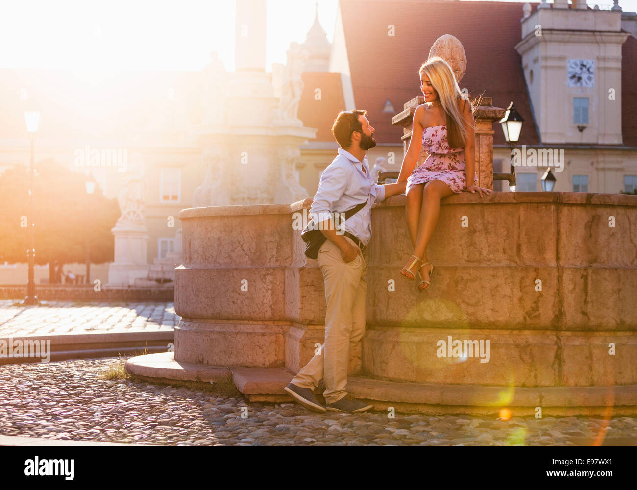 Jeune couple et le flirt par fontaine en ville Photo Stock