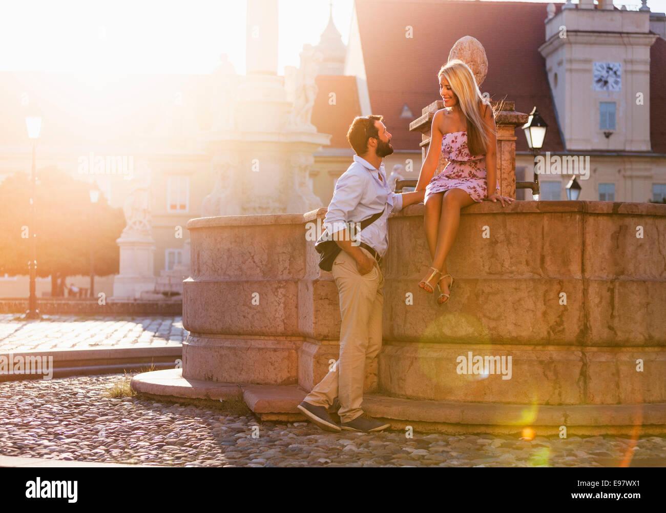 Jeune couple et le flirt par fontaine en ville Photo Stock