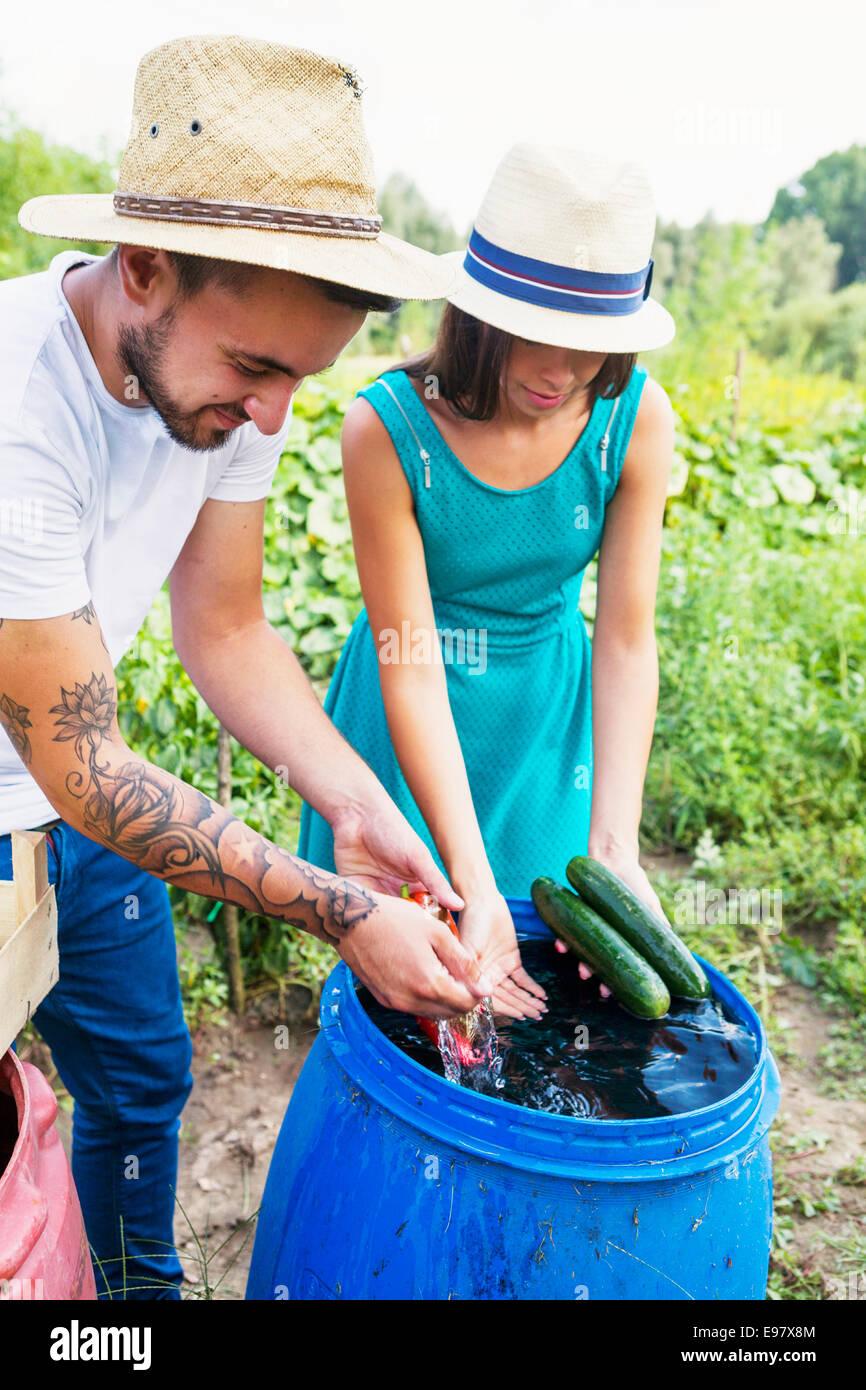 Jeune couple lave-légumes dans le baril Photo Stock