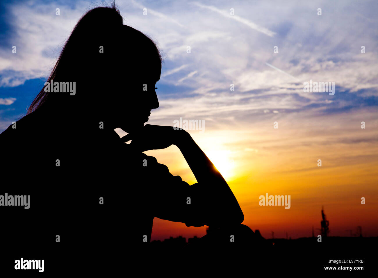 Silhouette of woman with hand on chin au coucher du soleil Photo Stock