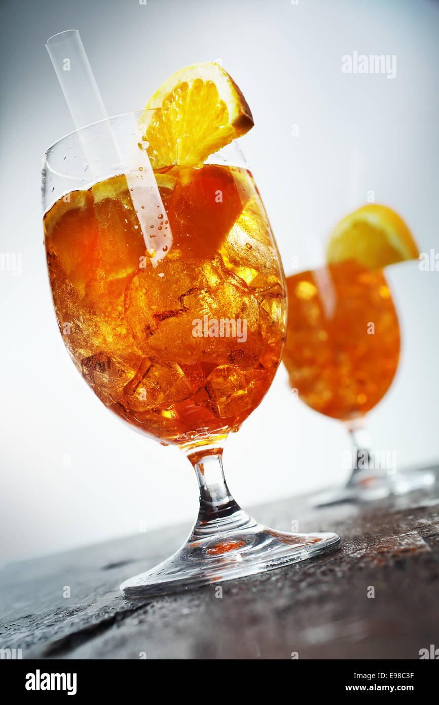 Golden orange et un cocktail au rhum aperol sprizz servi dans des coupes sur un vieux comptoir en bois haut, low Photo Stock