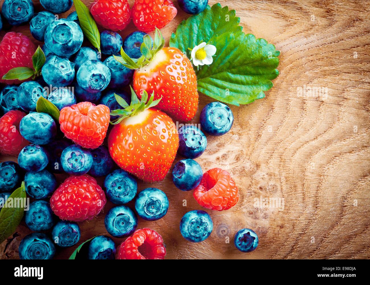 Vue supérieure de l'automne des baies mûres mixtes y compris les fraises, les framboises et les bleuets Photo Stock