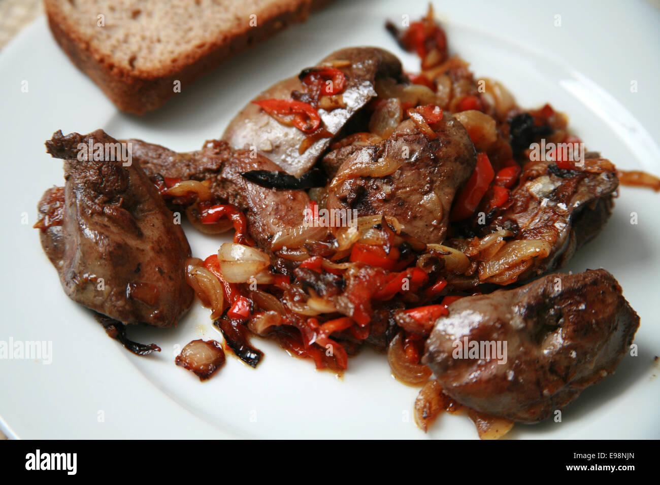 Foies de poulet frit avec des oignons et poivrons rouges caramélisés servi sur plaque blanche avec Brown Photo Stock