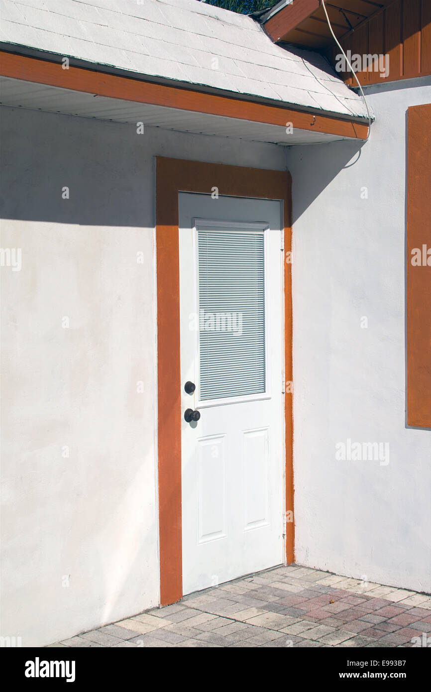 Soleil brille sur une porte blanche fermée sur une maison blanche avec garniture orange dans la région Photo Stock