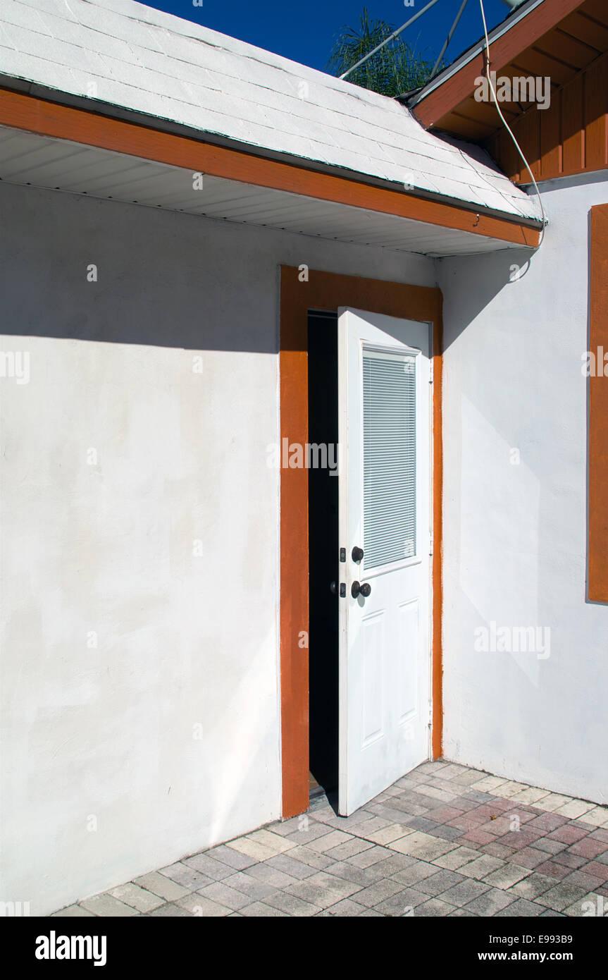 Soleil brille sur une légère ouverture porte blanche sur une maison blanche avec garniture orange dans Photo Stock