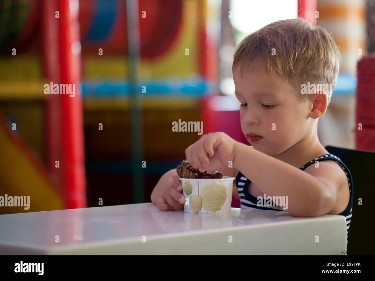 Petit enfant de manger de la crème glacée au chocolat Photo Stock