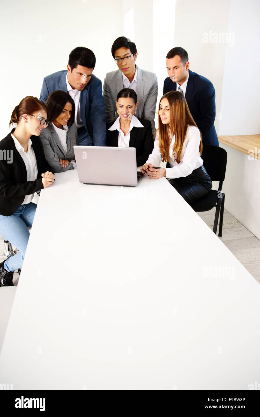 Un groupe de partenaires d'affaires using laptop together Photo Stock