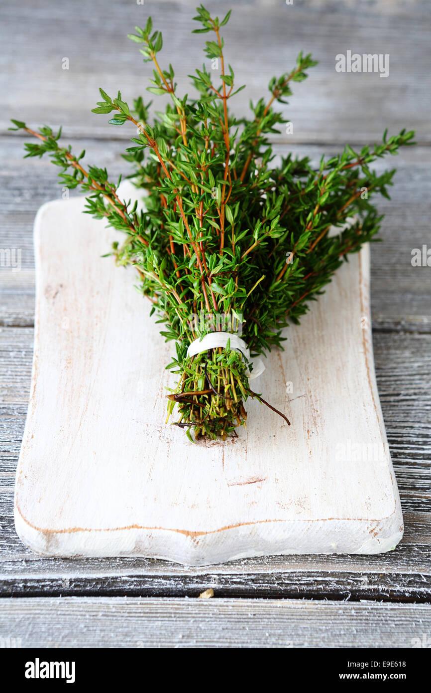 Thym parfumé sur une planche à découper, fond de bois Banque D'Images