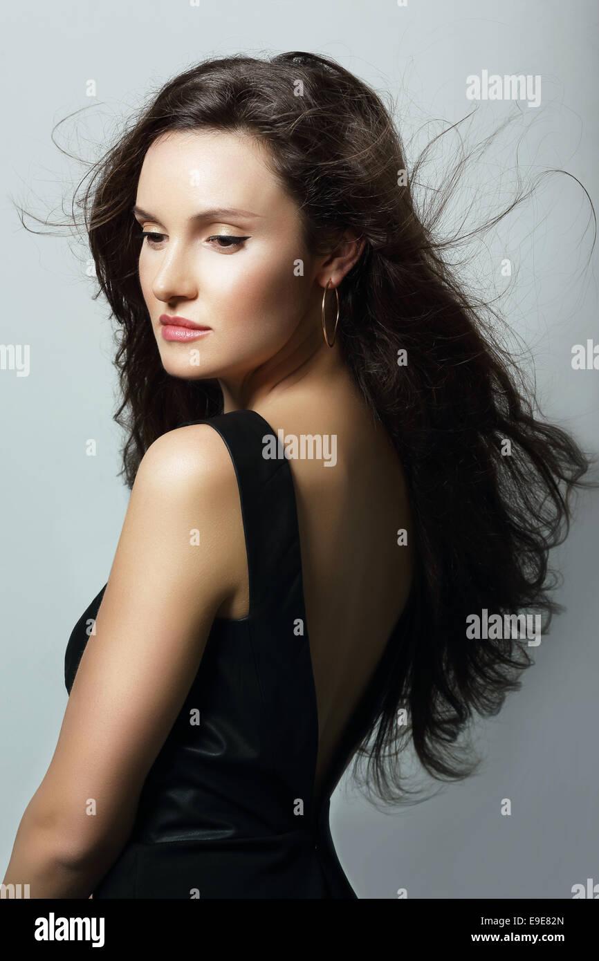 Charme. Dame aristocratique en robe noire et de longs cheveux Photo Stock