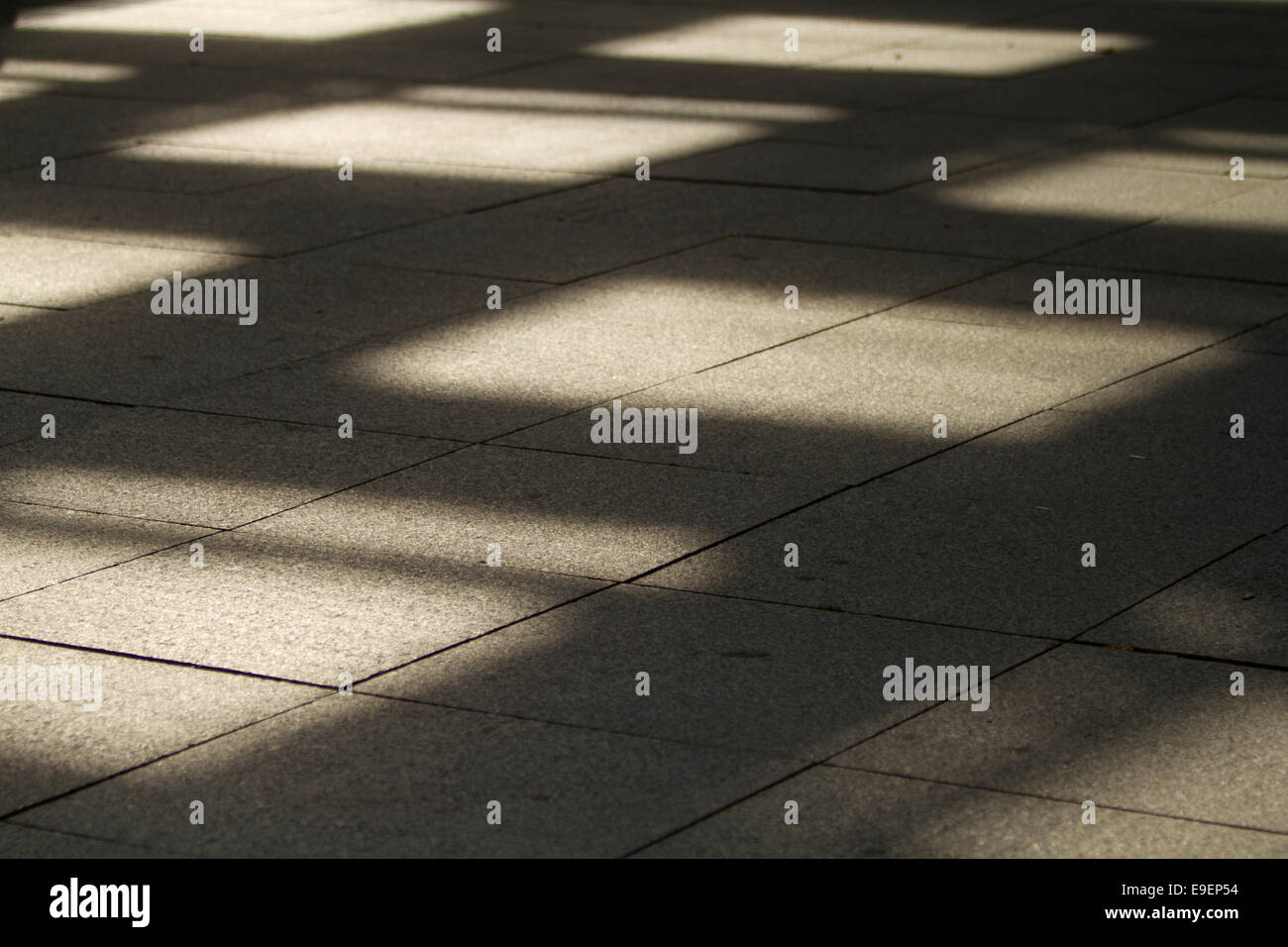 Les ombres sur les places de la grille de la chaussée texture Photo Stock