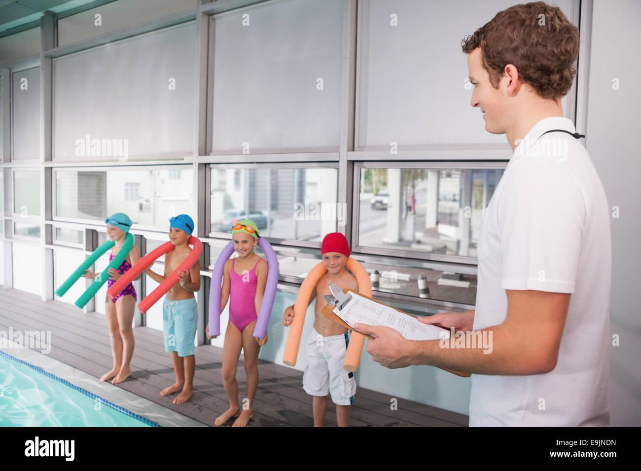 L'entraîneur de natation de la piscine holding clipboard Photo Stock
