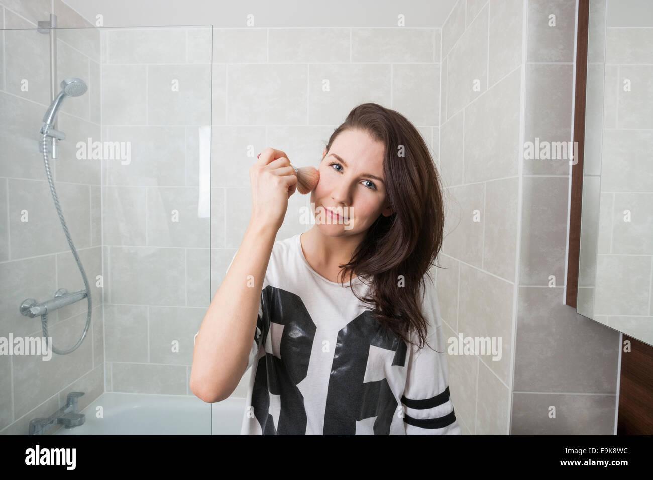 Portrait de femme belle appliquant le maquillage dans la salle de bains Photo Stock