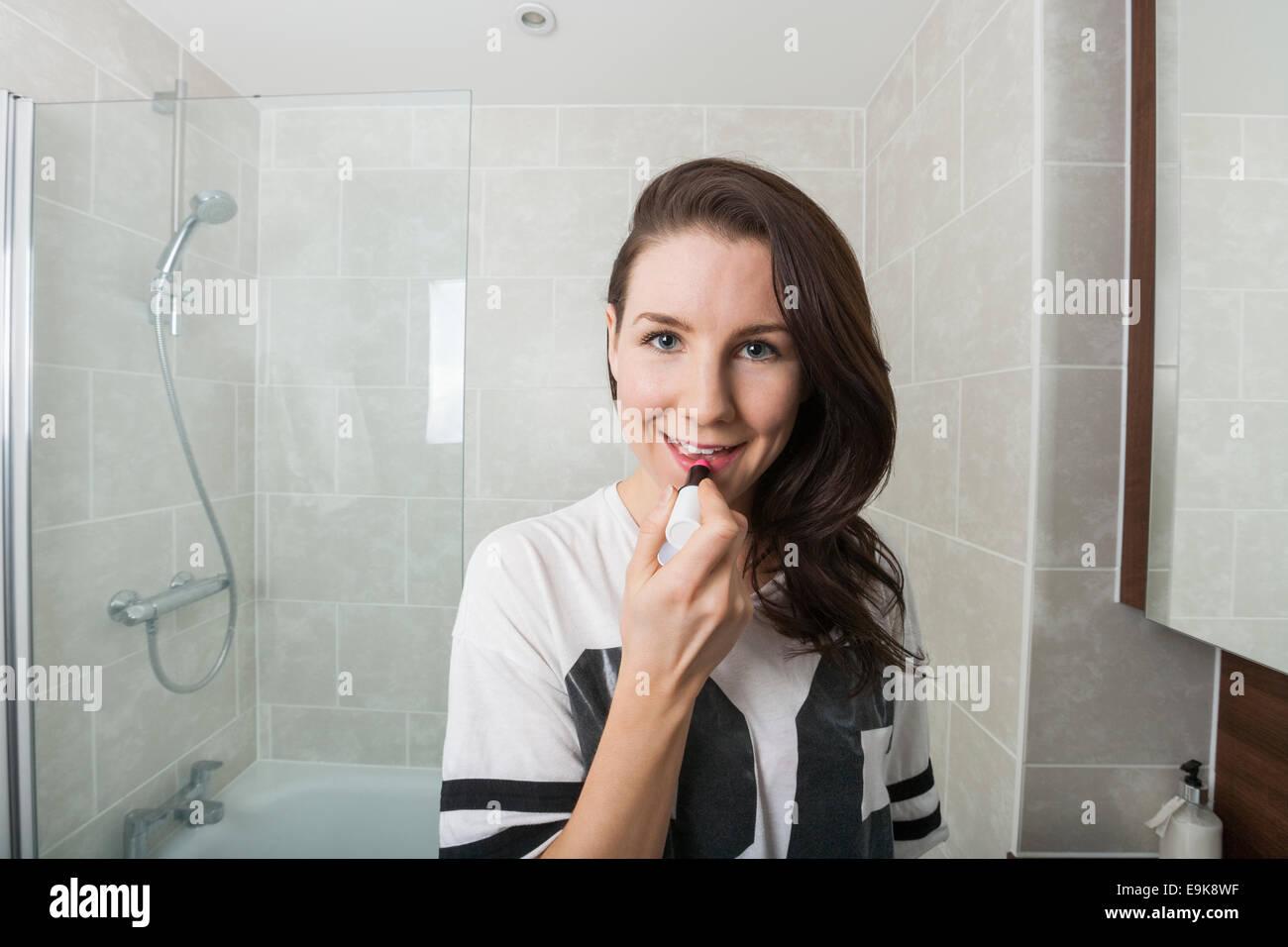 Portrait of young woman applying lipstick dans la salle de bains Photo Stock