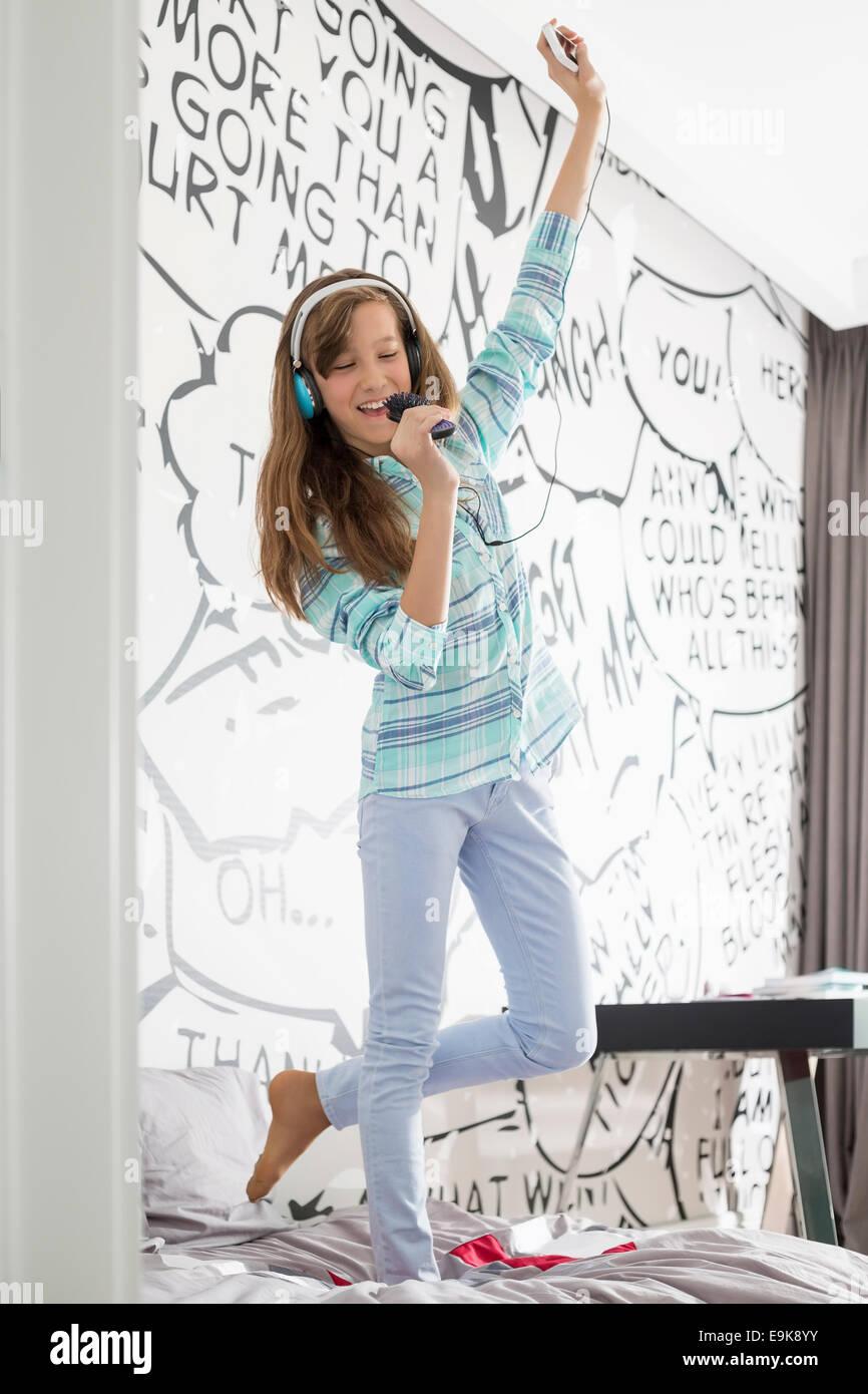 Fille de pleine longueur à l'écoute de la musique tout en chantant en brosse on bed Photo Stock