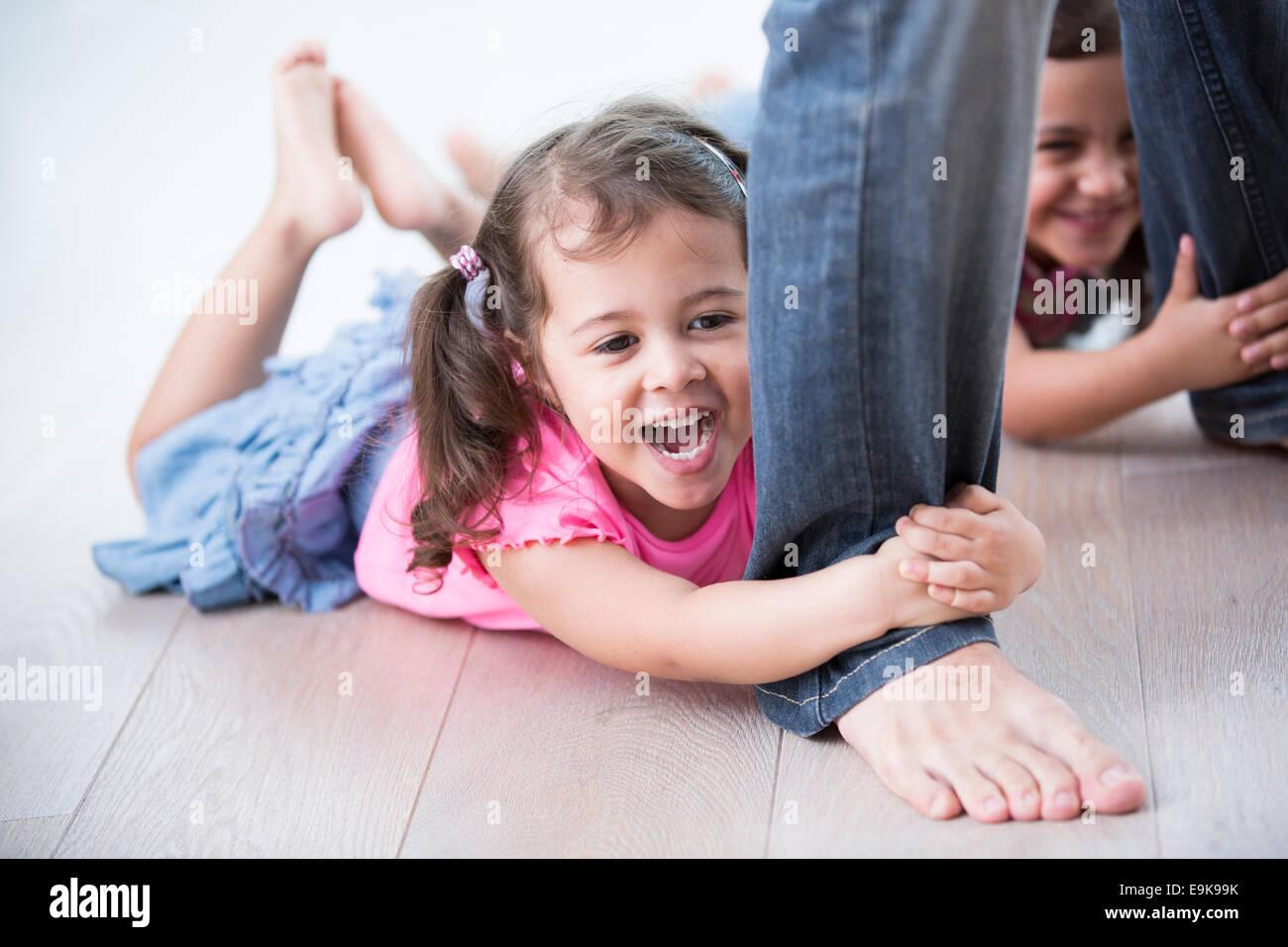 Girls holding ludique père jambes sur plancher de bois franc Photo Stock
