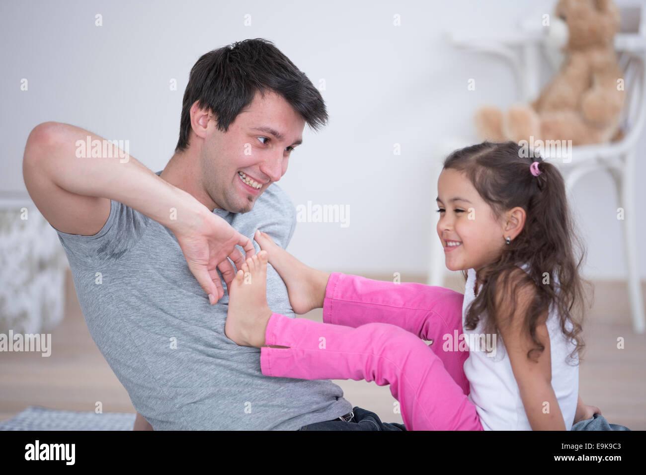 Père de chatouiller le pied de sa fille à la maison Photo Stock