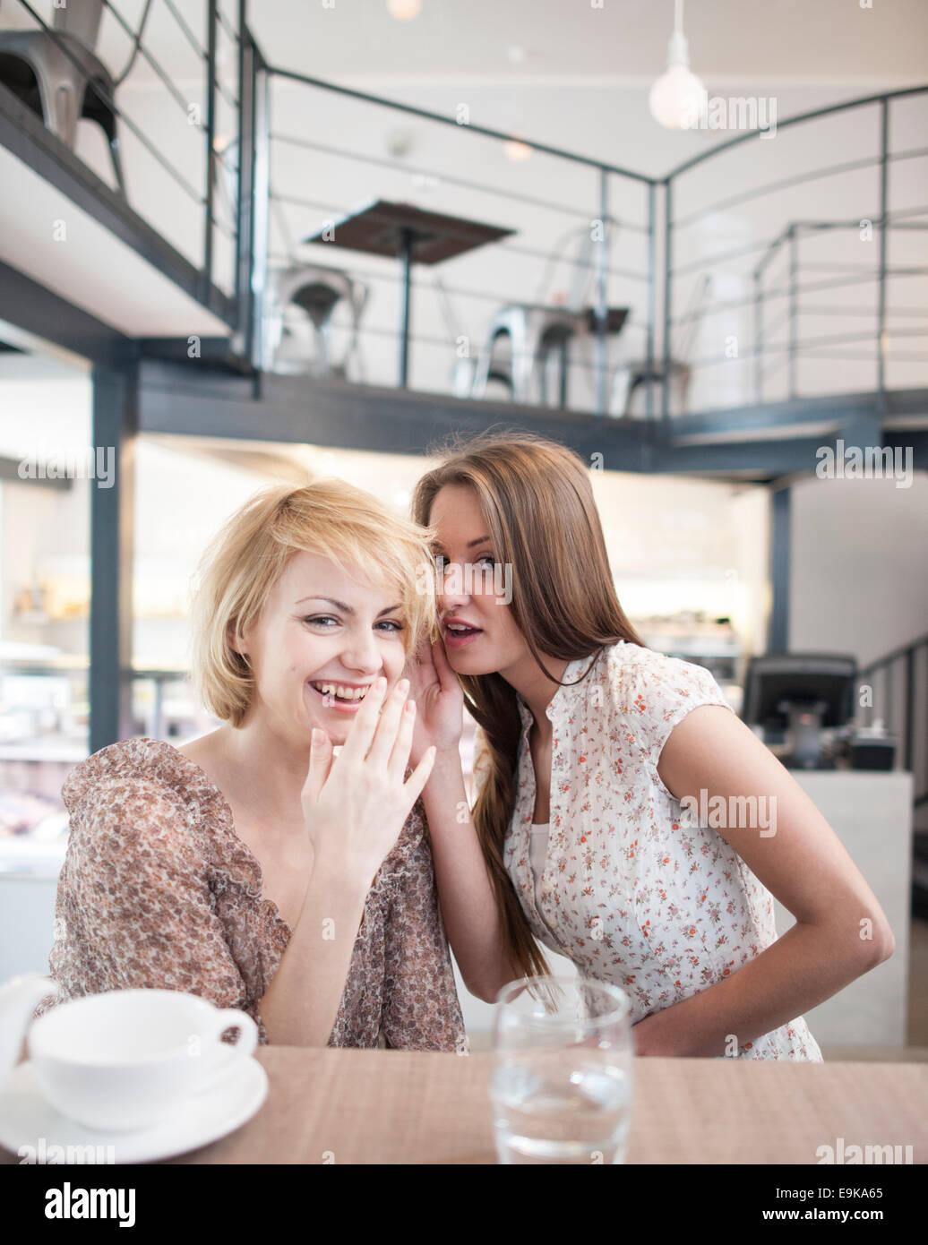 Portrait de jeune femme chuchotant à l'oreille amie in cafe Photo Stock