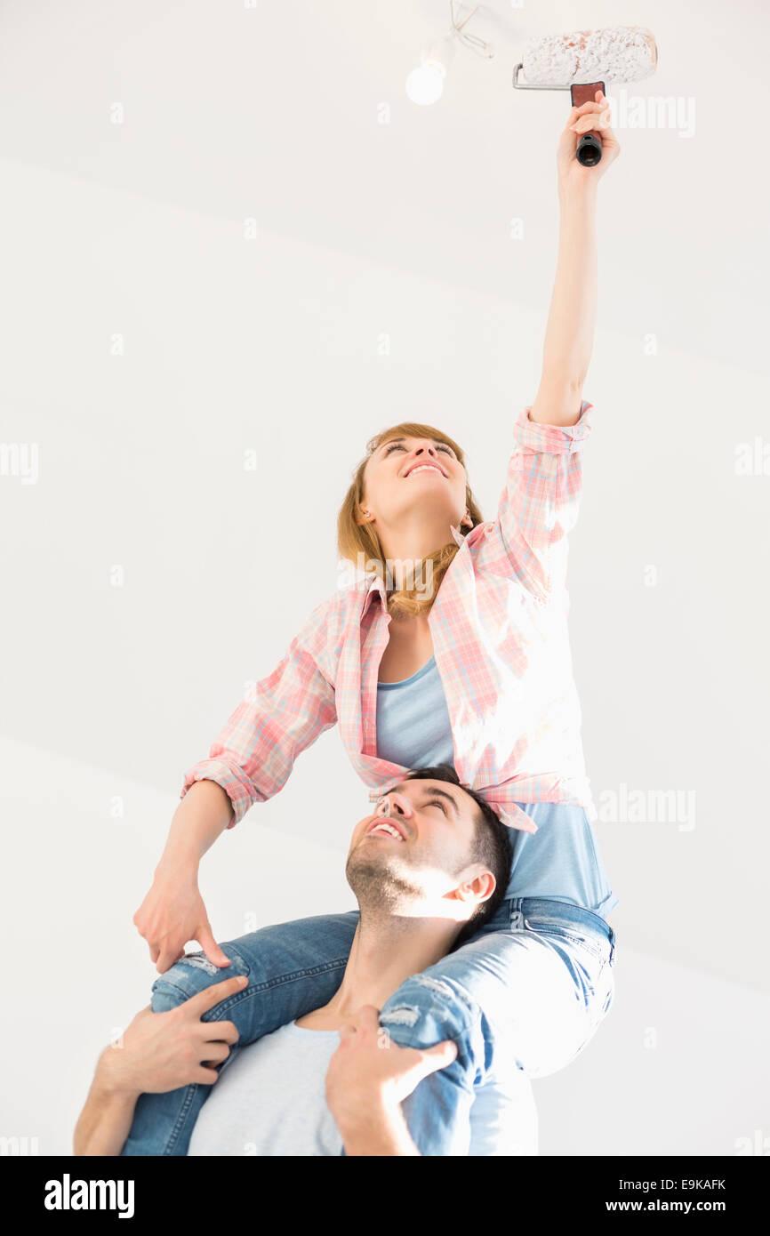 Femme sur les épaules de l'homme peinture plafond avec rouleau à peindre Photo Stock