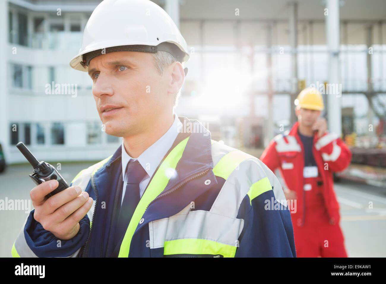 Travailleur à l'aide de talkie-walkie avec collègue en arrière-plan à cour d'expédition Photo Stock