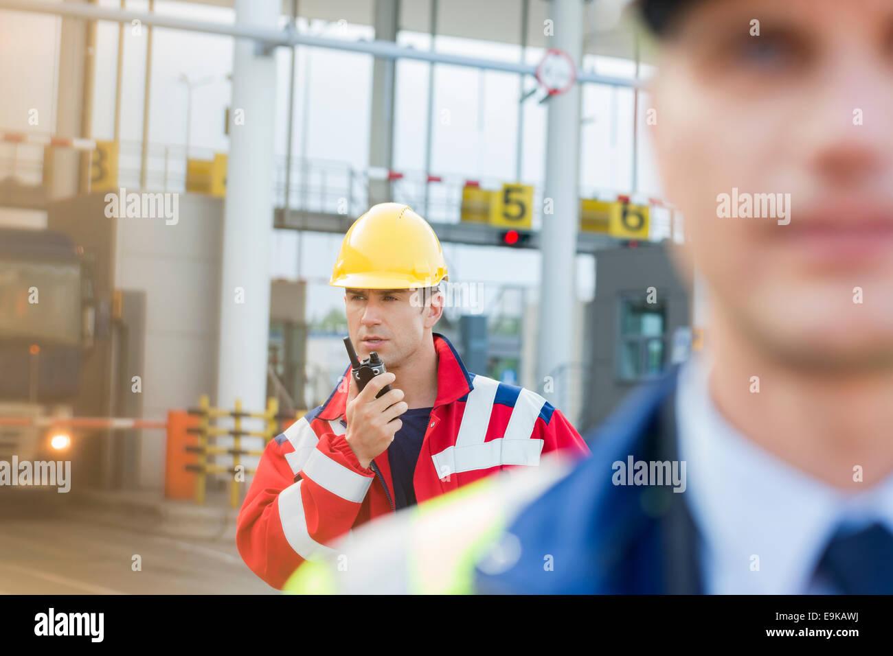 Travailleur à l'aide de talkie-walkie avec collègue en premier plan au Shipyard Photo Stock