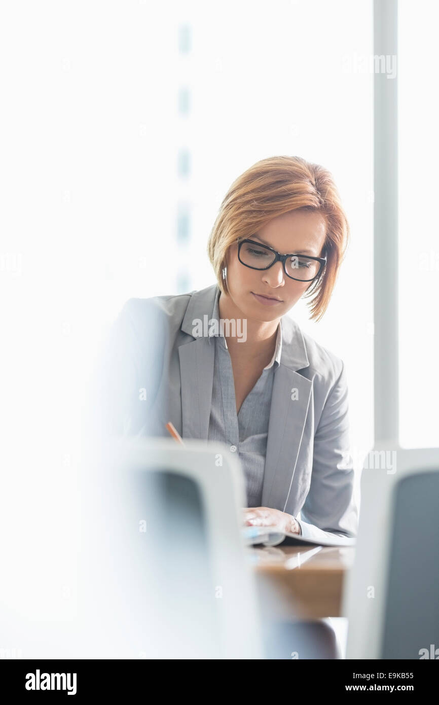 Jeune businesswoman writing at desk in office Photo Stock