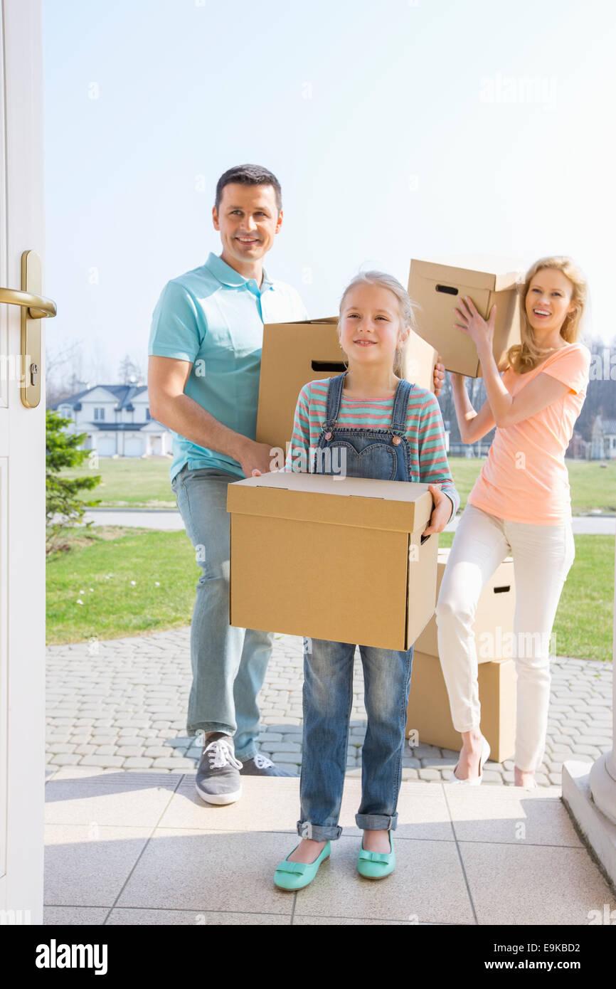 Famille avec boîtes de carton entrant dans nouvelle maison Photo Stock