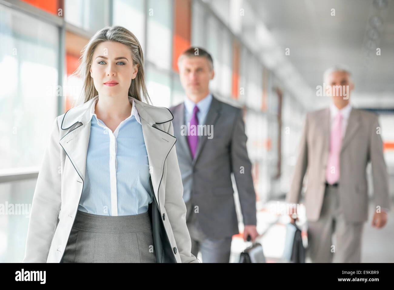 Belle jeune businesswoman walking avec des collègues masculins en arrière-plan à plate-forme du train Banque D'Images