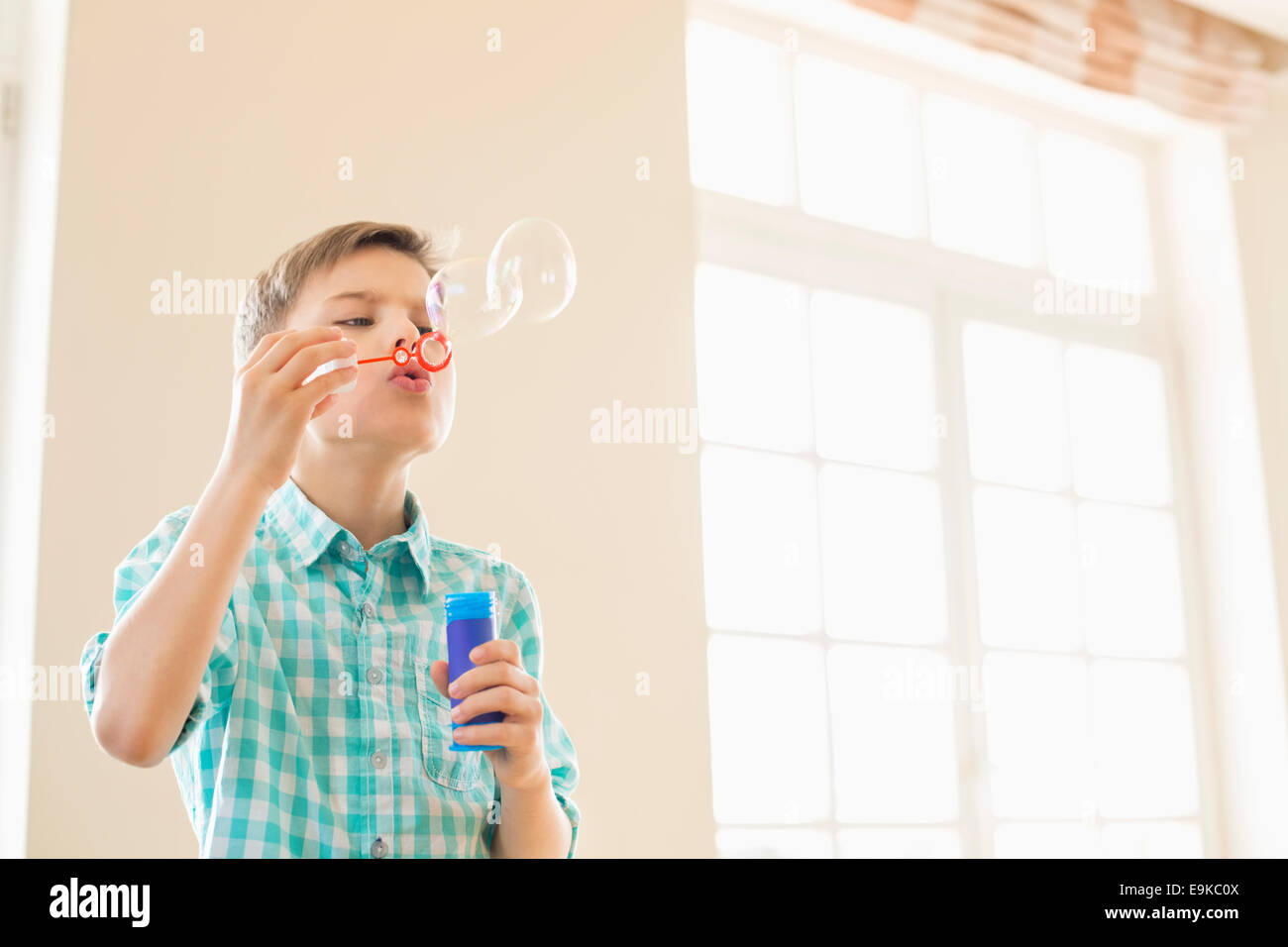 Boy blowing Bubbles at Home Photo Stock