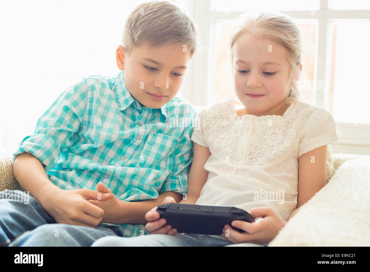 Frères et sœurs jouant un jeu vidéo à la maison Photo Stock