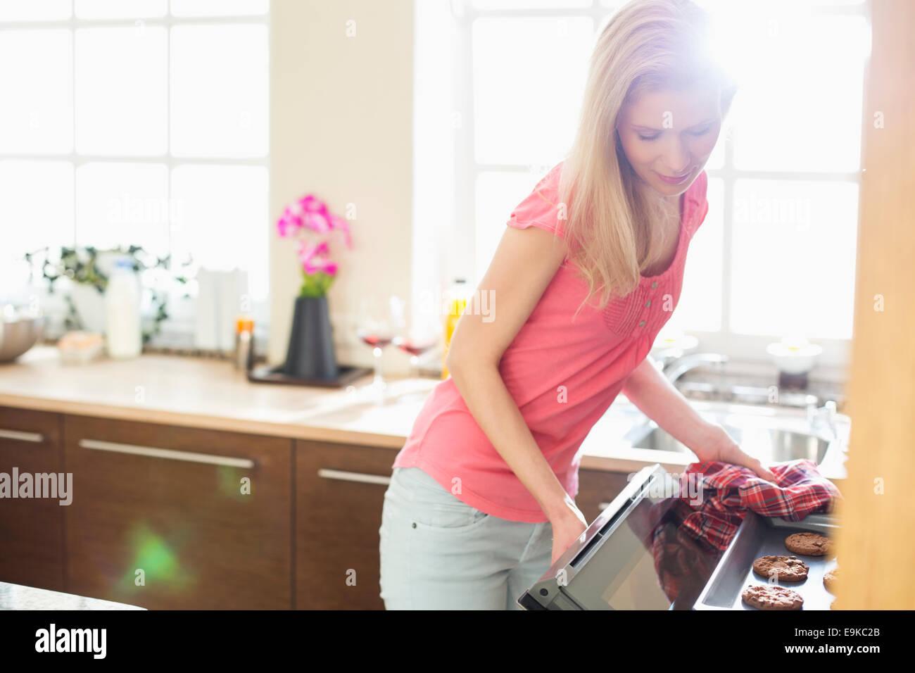 Mid adult woman baking cookies dans la cuisine Photo Stock