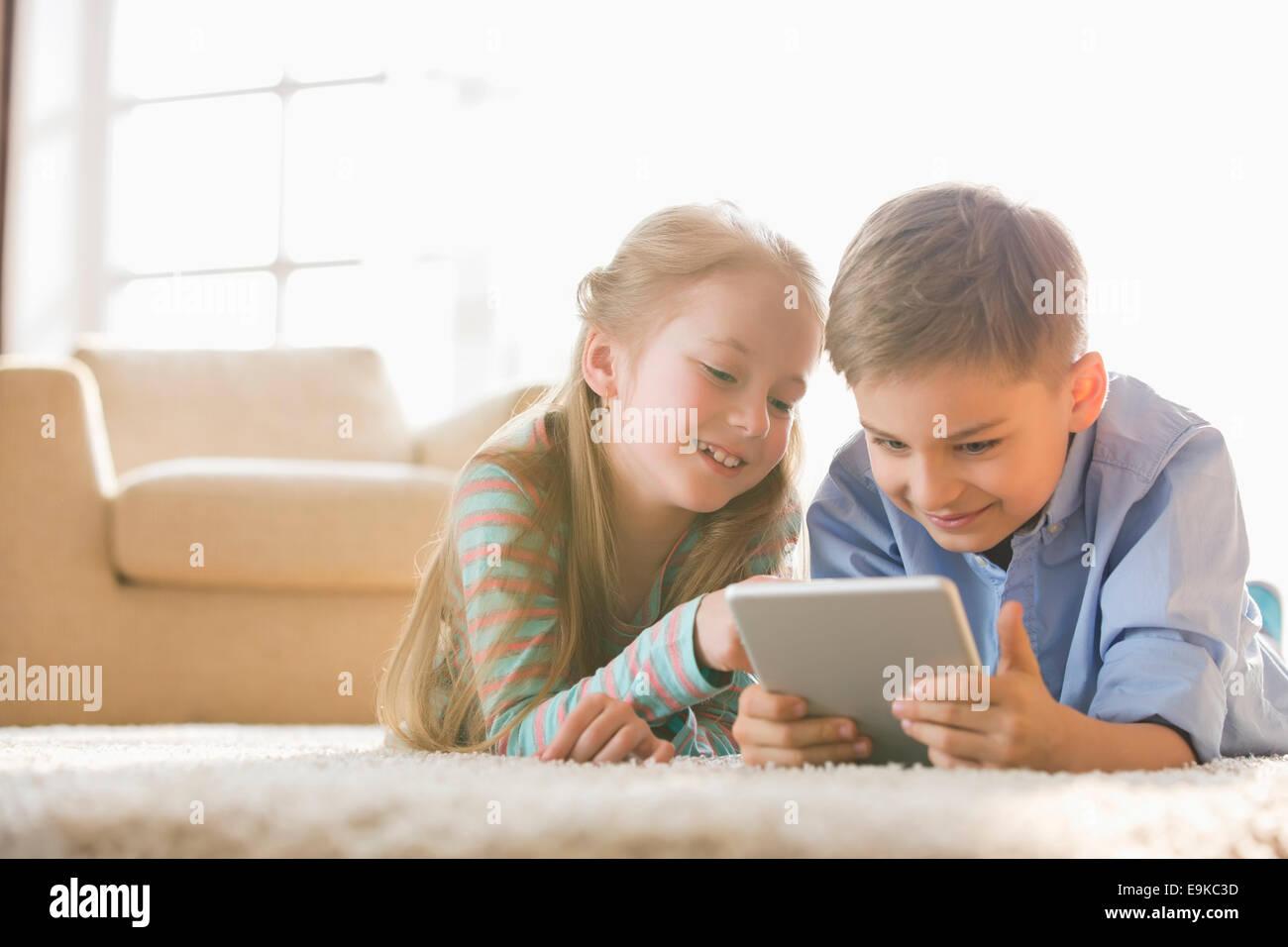 Brother and sister using digital tablet sur le plancher à la maison Photo Stock