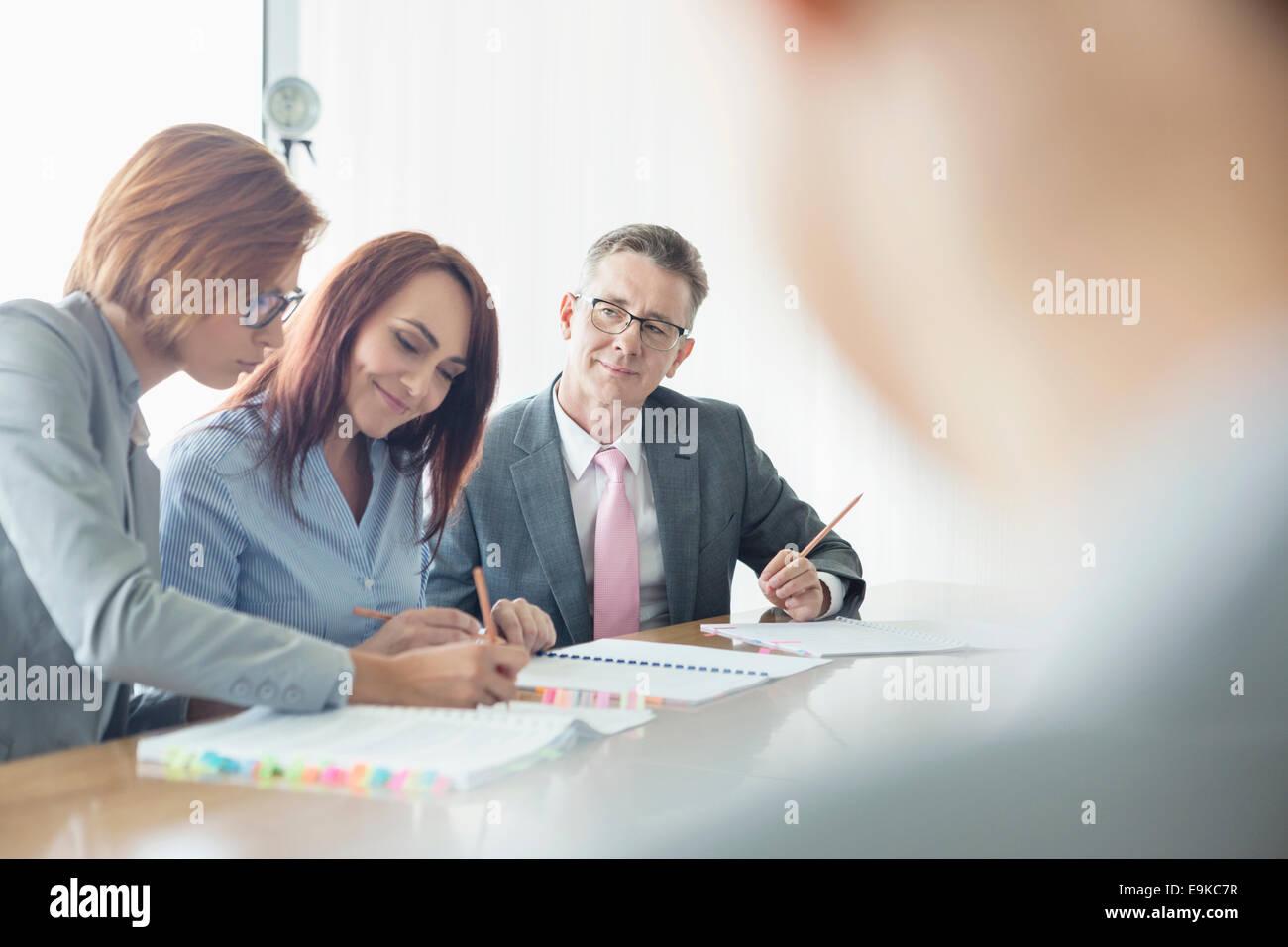 Les gens qui travaillent ensemble à la table de conférence Photo Stock