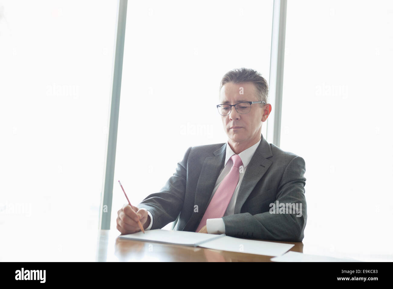 Mature businessman écrit le livre à table in office Photo Stock