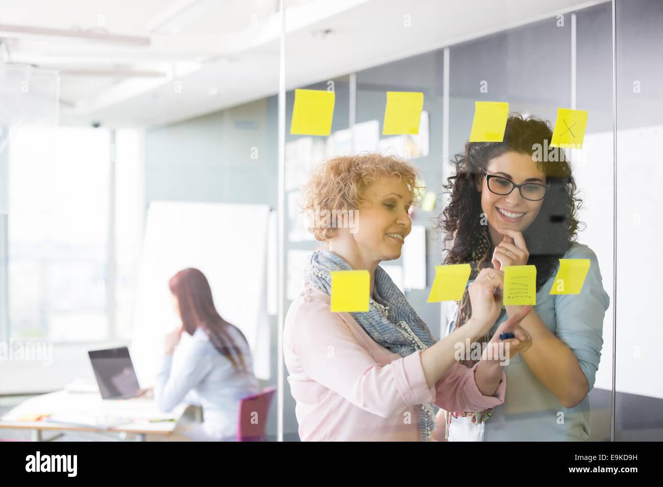 Les femmes d'affaires remue-méninges avec les notes in office Photo Stock