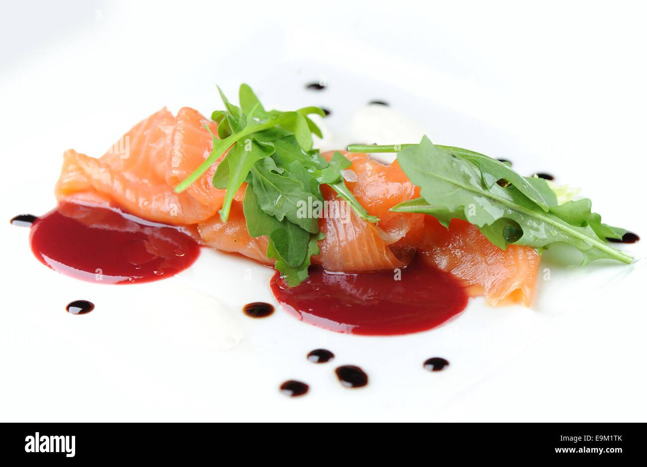 Gravlax de saumon fumé servi en entrée sur une assiette blanche avec la sauce chili. Photo Stock
