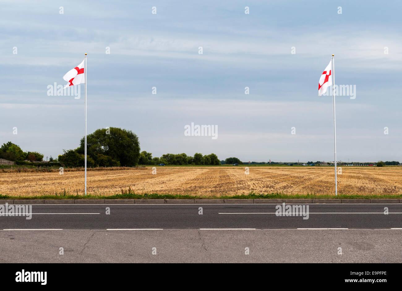 Deux mâts battant St George's Cross se tenir au bord de la route à Romney Marsh, Kent, UK Photo Stock