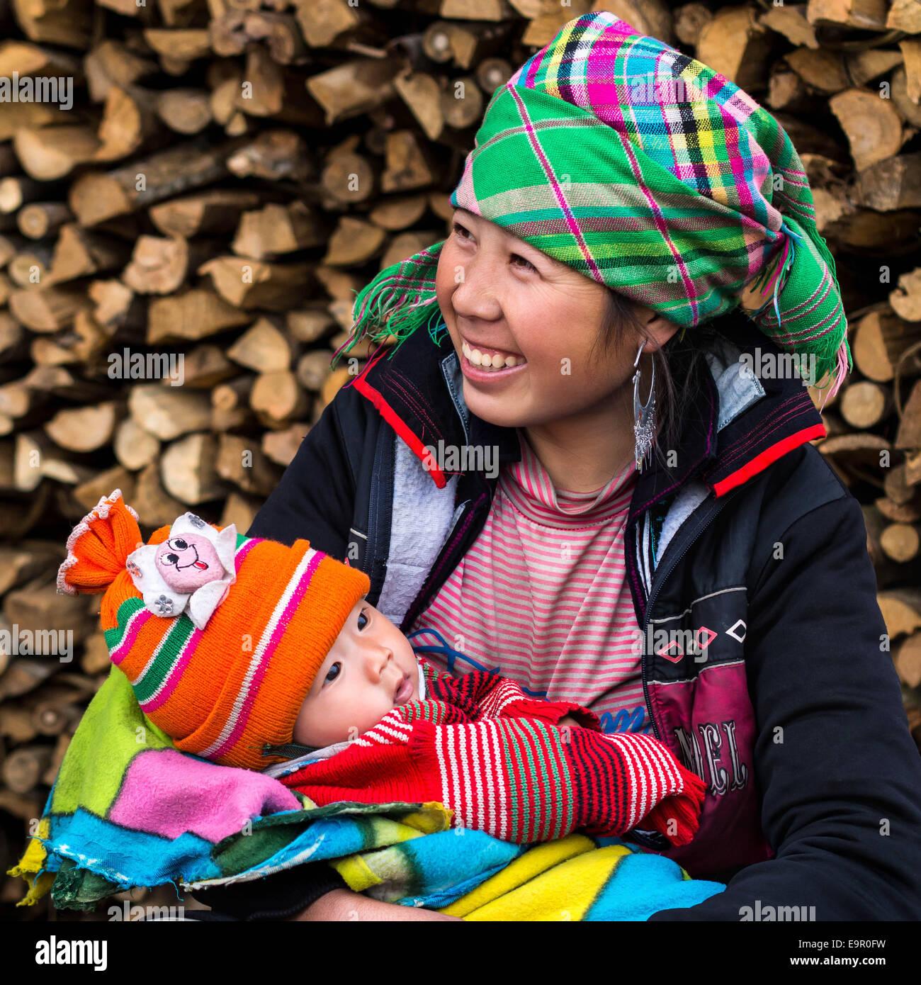 Femme Hmong heureux avec bébé, souriant, assis dehors au village Ta Van près de Sapa, province de Photo Stock