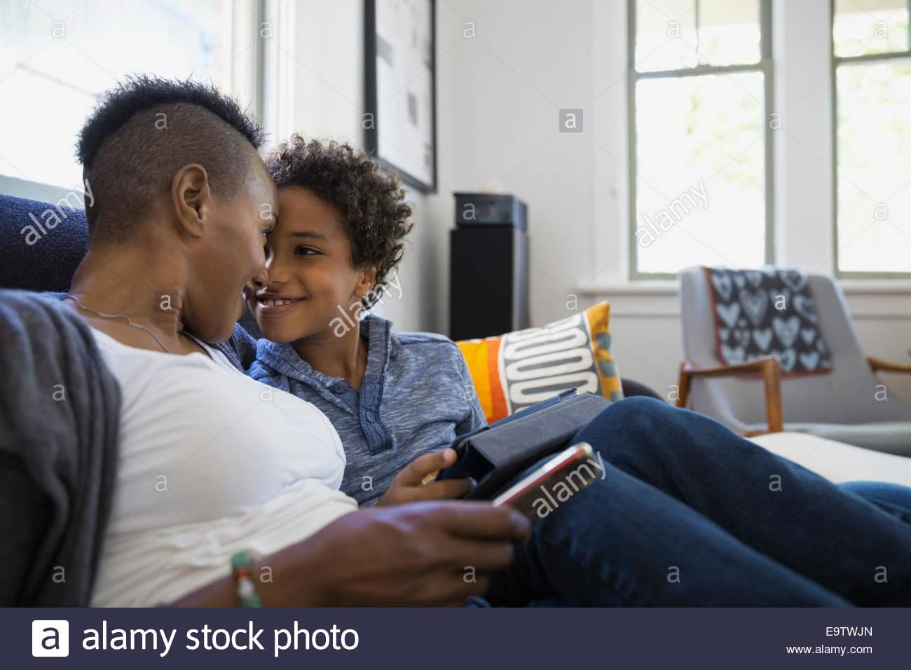 Mère et fils rubbing noses sur canapé Photo Stock