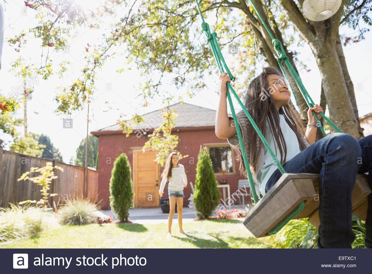 Fille sur tree swing en arrière-cour ensoleillée Photo Stock