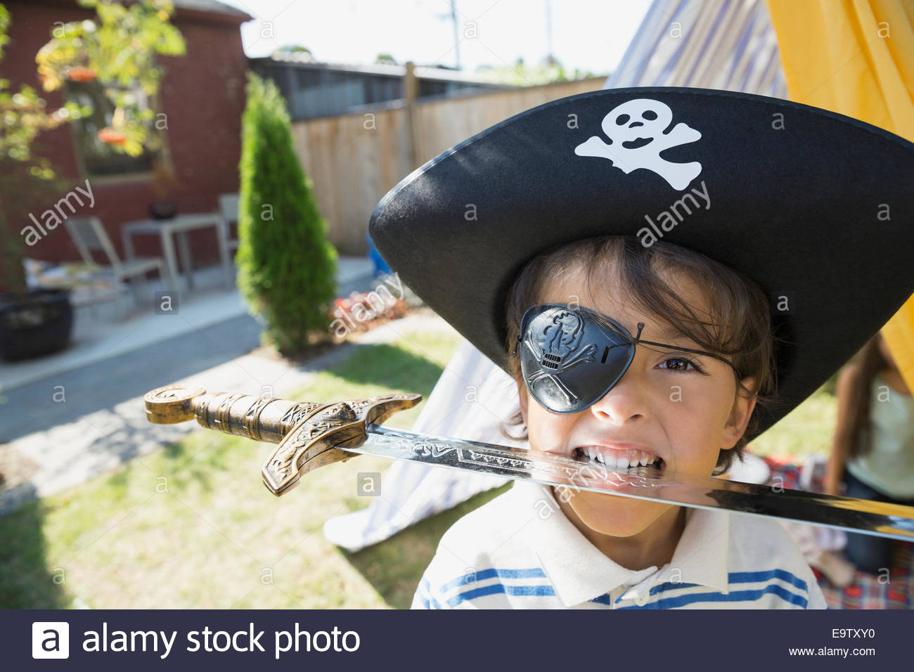 Portrait of boy in pirate hat biting sword Photo Stock