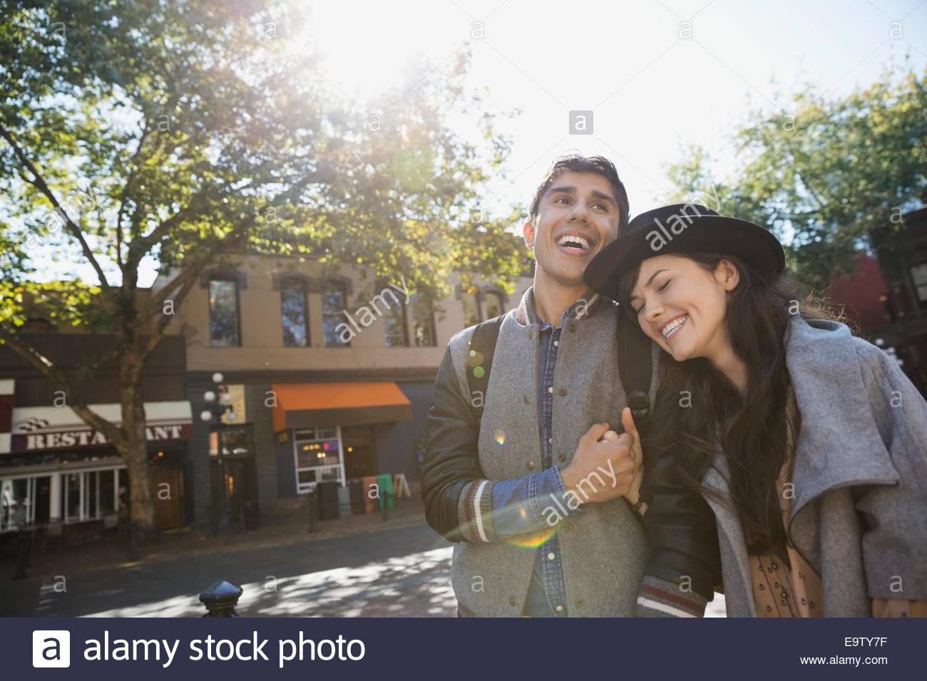 Couple laughing on sunny urban street Photo Stock