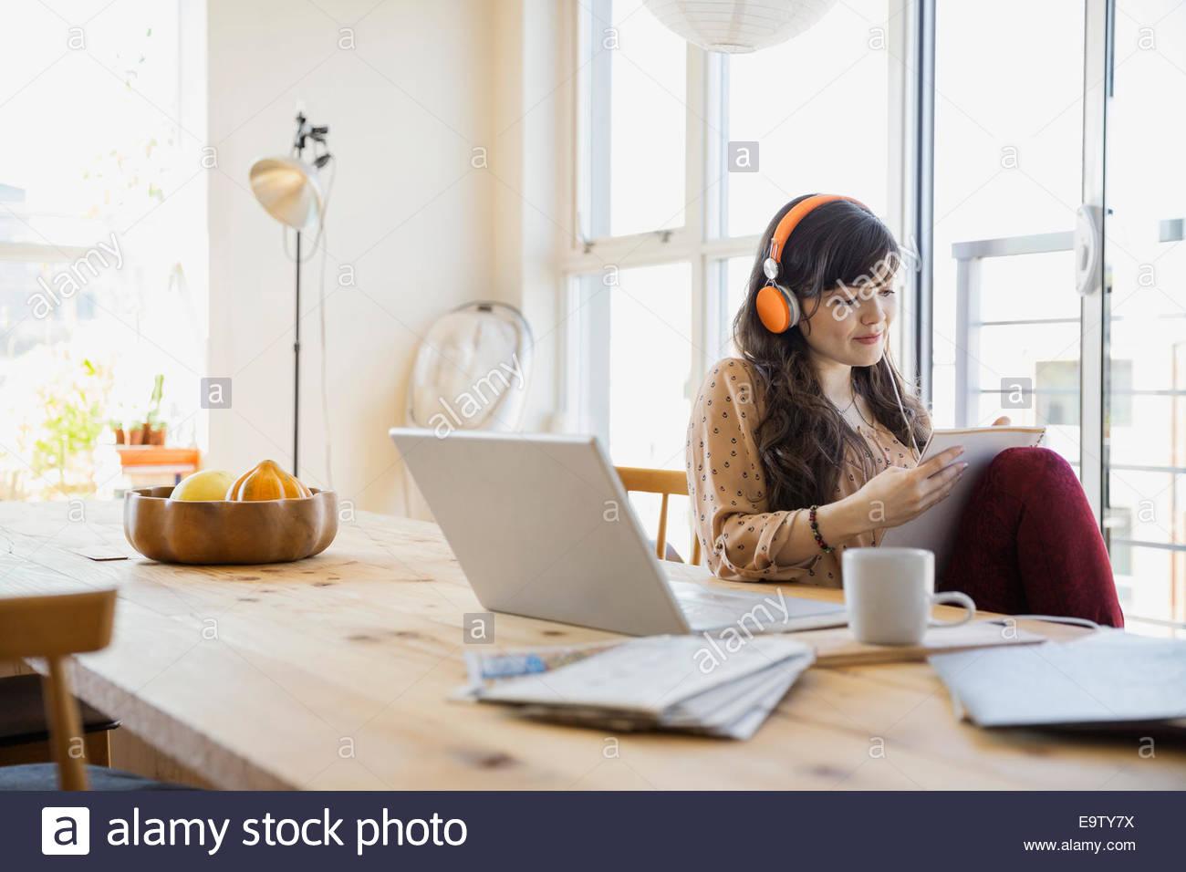 Femme avec casque et à l'ordinateur portable ordinateur portable Photo Stock