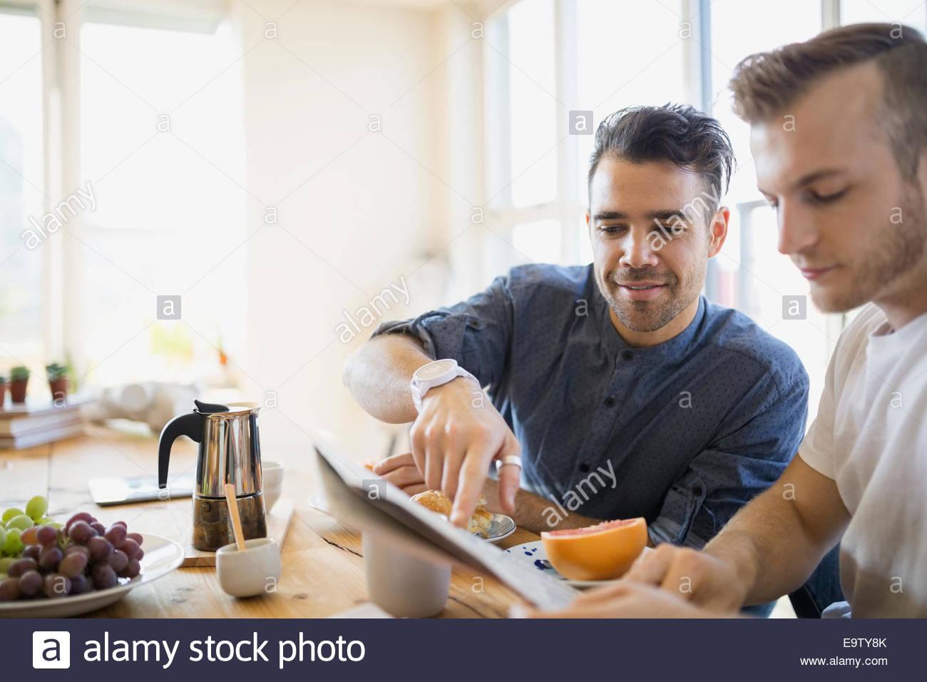 Couple homosexuel journal de lecture et prendre le petit-déjeuner Photo Stock