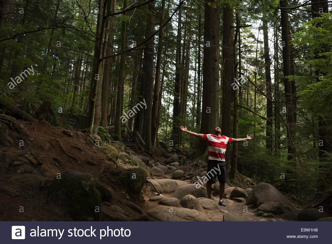 Homme exubérant avec bras tendus dans les bois Photo Stock