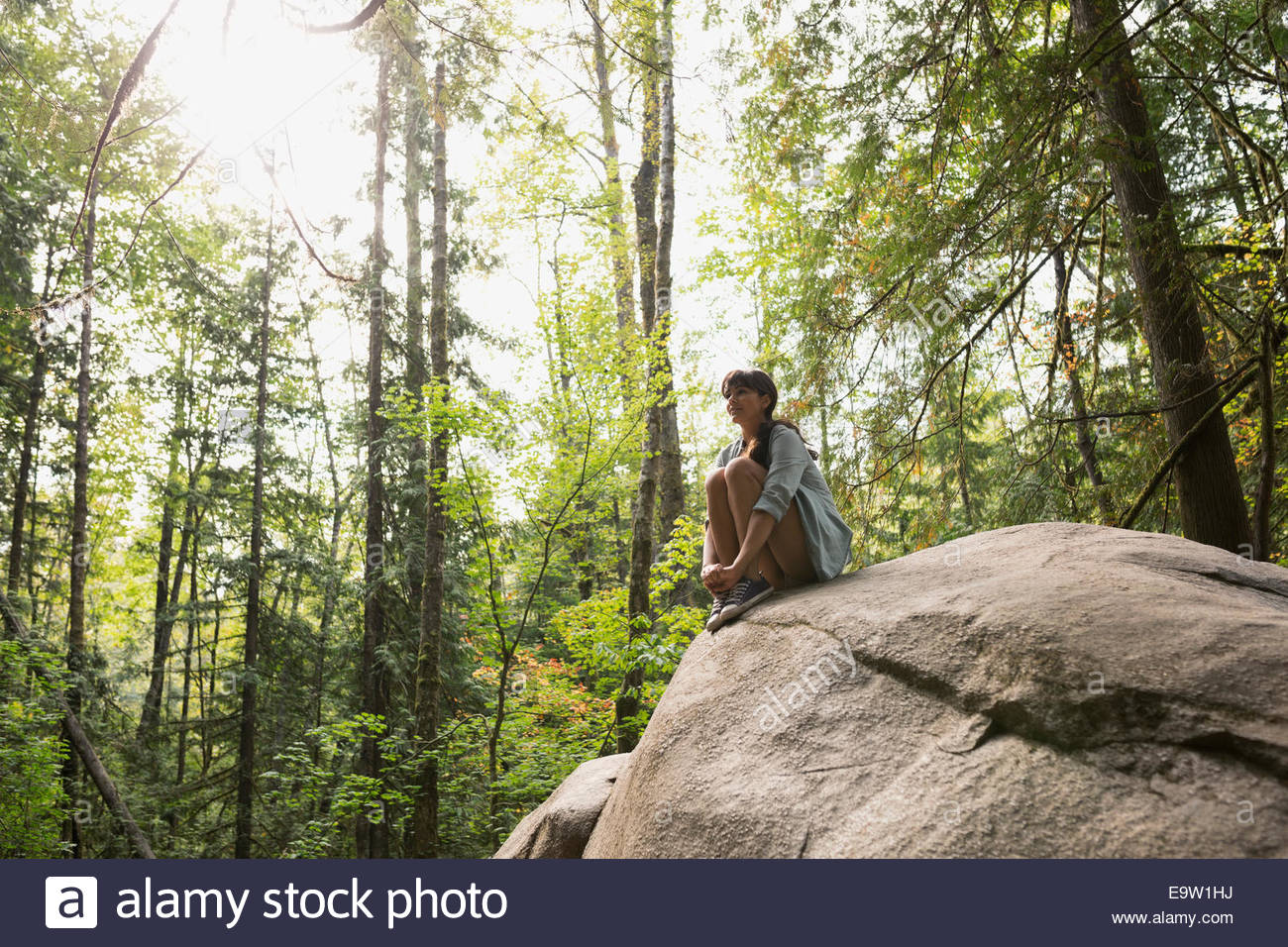 Young woman sitting on rock in sunny woods Photo Stock