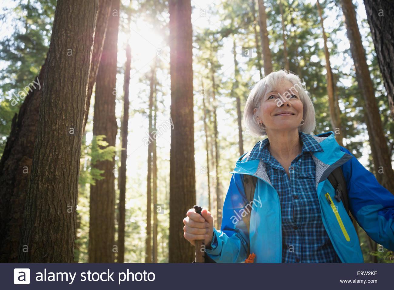 Smiling senior woman hiking ci-dessous des arbres dans les bois Photo Stock